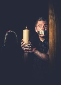 Author photo of alarmed looking Darren Shan in a darkened room, duck tape over his mouth and bound hands holding a candle, with a sinister young girl lurking in the background
